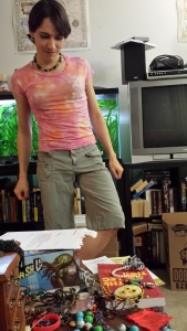 A 20something woman with short hair, wearing eyeshadow, a necklace, a pink tie-dyed T-shirt, and knee-length gray-green shorts, surrounded by piles of plastic jewelry, clothes, and board games.