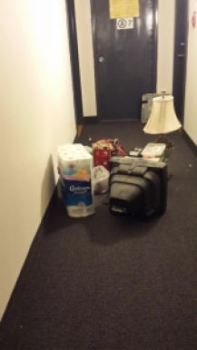 Hallway with items left behind by movers including TV, toilet paper, a lamp, and more