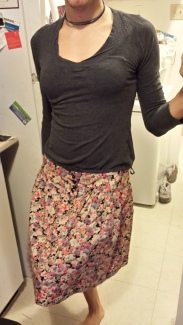 A gray long-sleeved top with a loose, densely patterned pink floral skirt