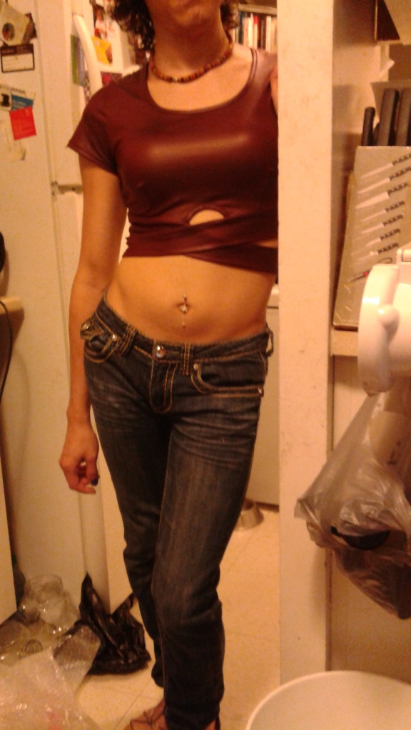 A mid-length wine-red crop top with strappy accents , skinny jeans, waist chain, dangly navel piercing, and wooden necklace with strappy sandals.